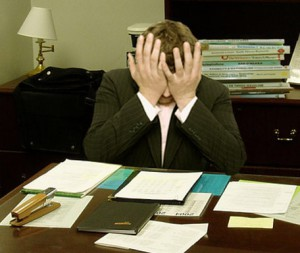 A man sitting at a desk looking frustrated